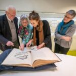 Jan Lindenbergh and his daughter look through Merian's book with WUR president Louise Fresco. On the right, curator Liesbeth Missel of the WUR Library.