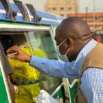 Man deelt mondkapjes uit in Sierra Leona