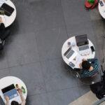 Studenten in het Forumgebouw, één per tafeltje