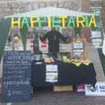 Happietariakraam op de markt in Wageningen boxen te verkopen.