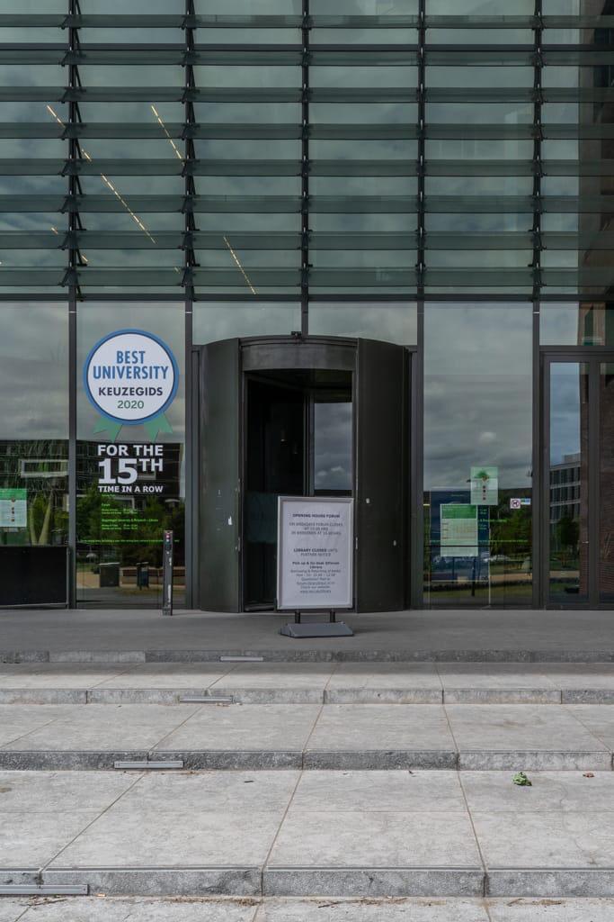 Ingang Atlasgebouw met poster 'beste universiteit 2020'