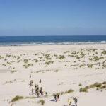 Studenten lopen door de duinen naar de zee